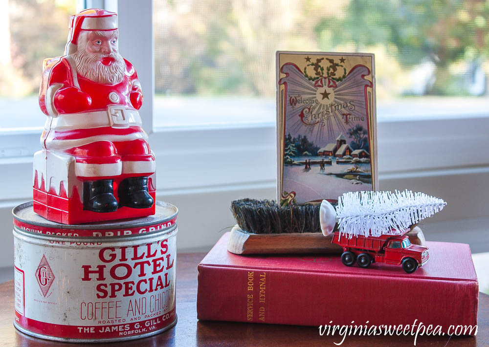 Vintage Santa, vintage Gill's Hotel Special coffee can, 1910 Christmas postcard, vintage shoe brush, vintage Matchbox truck and a 1958 hymnal.