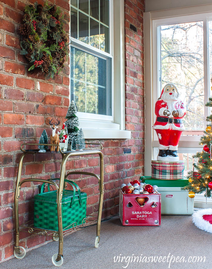 A Very Vintage Christmas on the porch - Vintage tv stand decorated for Christmas, vintage Santa blow mold, vintage Saratoga Dairy milk crate, and a vintage Coleman cooler.