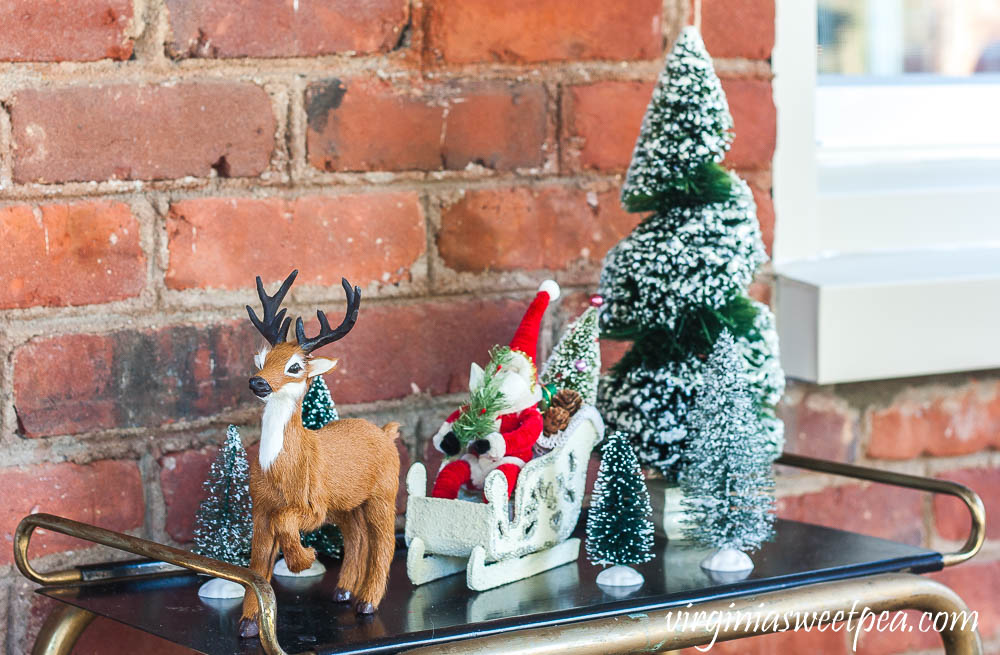 Byer's Choice reindeer with a Santa in his sled from the Vermont Country Store traveling through a forest of bottlebrush trees