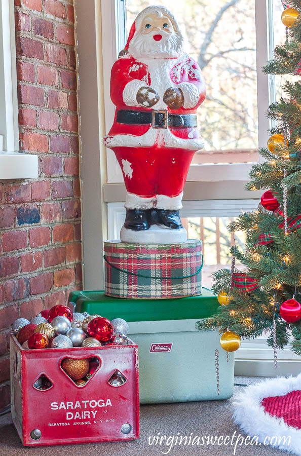 A Very Vintage Christmas on the Porch - Blow mold Santa, vintage plaid hat box, vintage Coleman cooler, and a vintage Saratoga Dairy milk crate filled with ornaments.