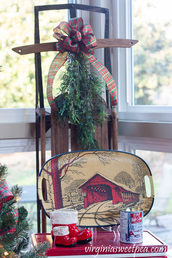 A Very Vintage Christmas on the Porch - Vintage sled decorated with a bow and greenery, vintage Coleman cooler with vintage Santa boots, a vintage covered bridge tray, and a maple syrup scented candle in a maple syrup can