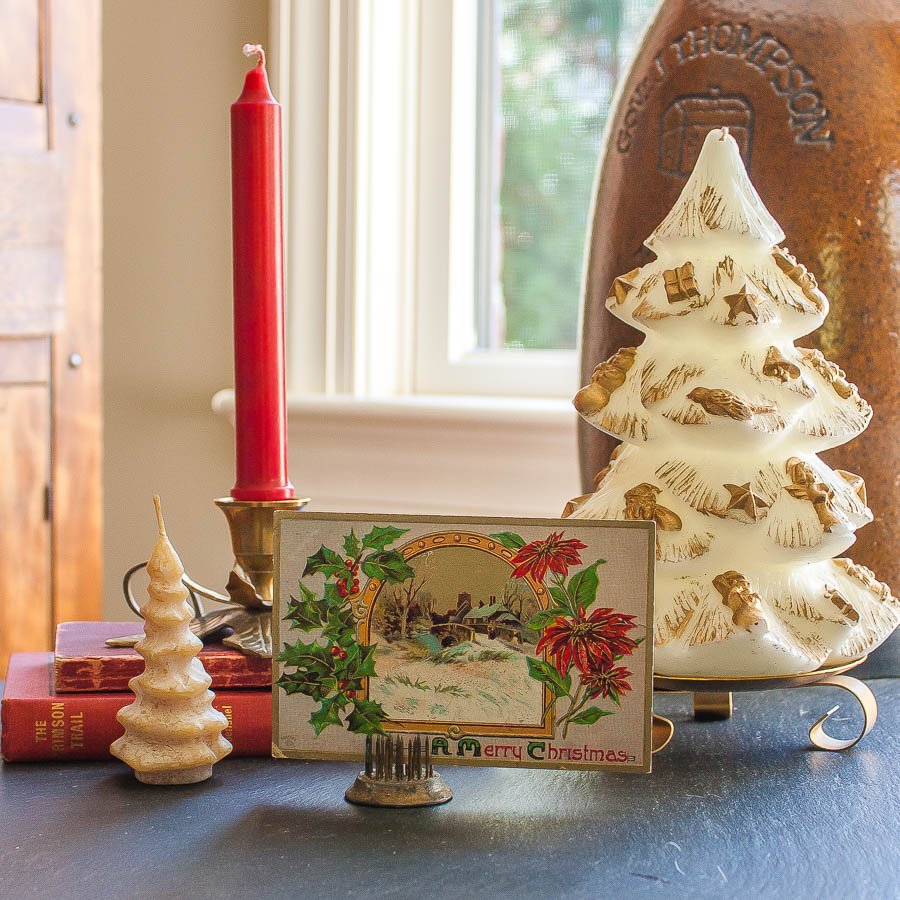 Christmas vignette with an early 1900's postcard, vintage Christmas tree candles, a vintage brass holly candle holder, a 1912 edition of The Crimson Trail by Elmer U. Hoenshel, and a 1903 edition of Ropp's New Calculator.