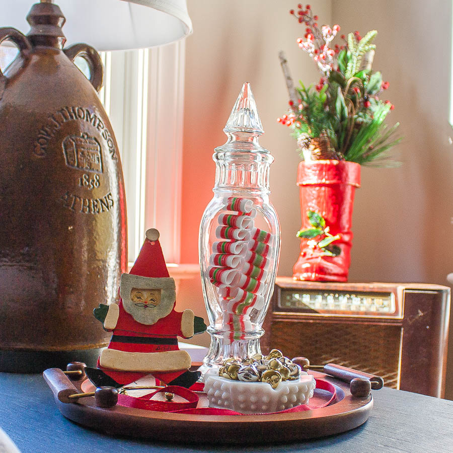 Christmas vignette with an antique Santa boot, vintage candy jar, 1970 Santa ornament, and a hobnob milk glass candy dish filled with jingle bells.