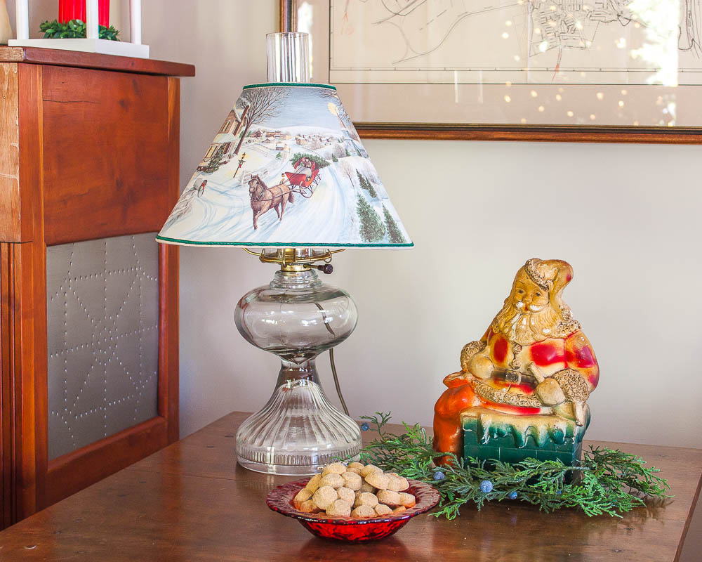 Antique lamp with a Christmas lamp shade with holes that illuminate the scene on it, vintage Santa bank, and a reindeer bowl filled with dog treats