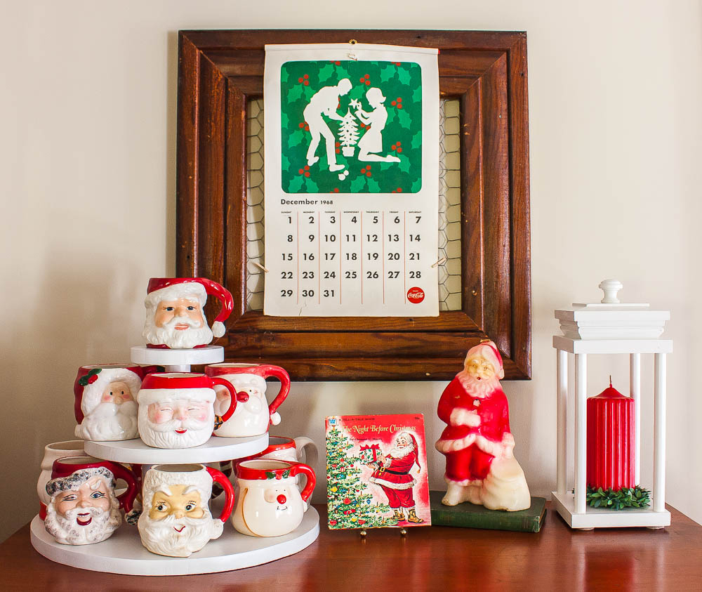 1968 Coca-Cola calendar, collection of vintage Santa mugs, 1976 The Night Before Christmas Book, vintage Santa candle, and a lantern holding a red candle