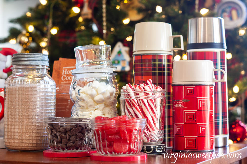 Hot Chocolate Bar with Vintage - Vintage jelly jars holding chocolate chips and cinnamon candy, a Nescafe jar holding peppermint sticks, and a trio thermoses.