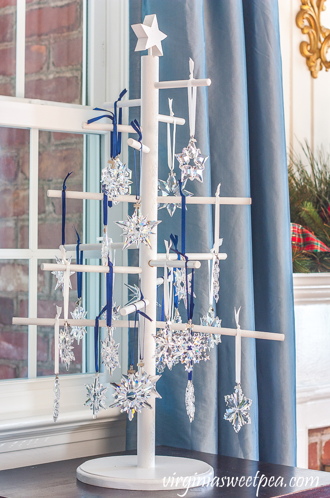 A wooden tree displaying Swarovski snowflake Christmas ornaments dated from 1993 - 2019