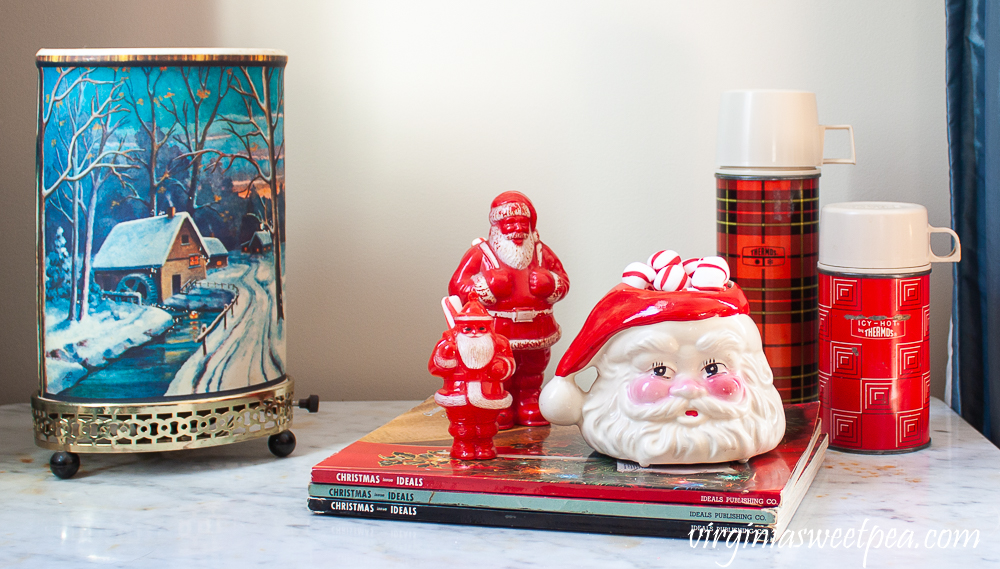 Vintage winter scene Econolite motion lamp, Christmas Ideals books from the 1960's, vintage plastic Santa candy holders, vintage Santa mug, and two vintage thermoses