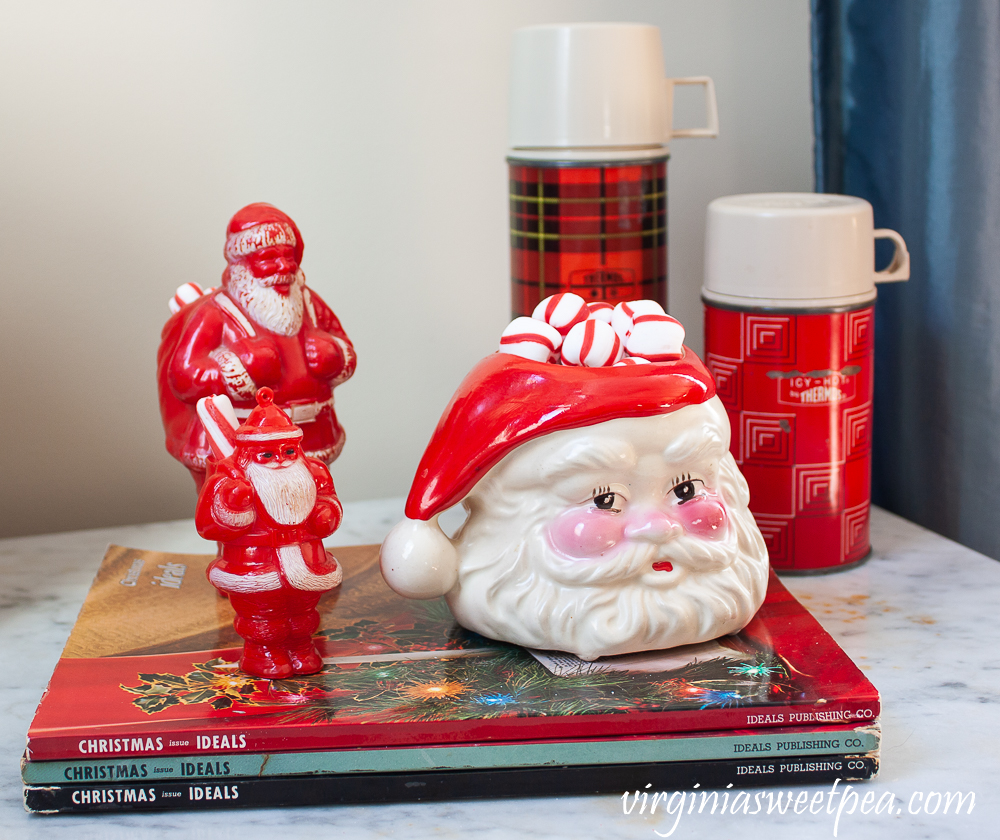 Vintage Christmas Ideals books, vintage plastic Santa candy holders, vintage Santa Christmas mugs, vintage thermoses