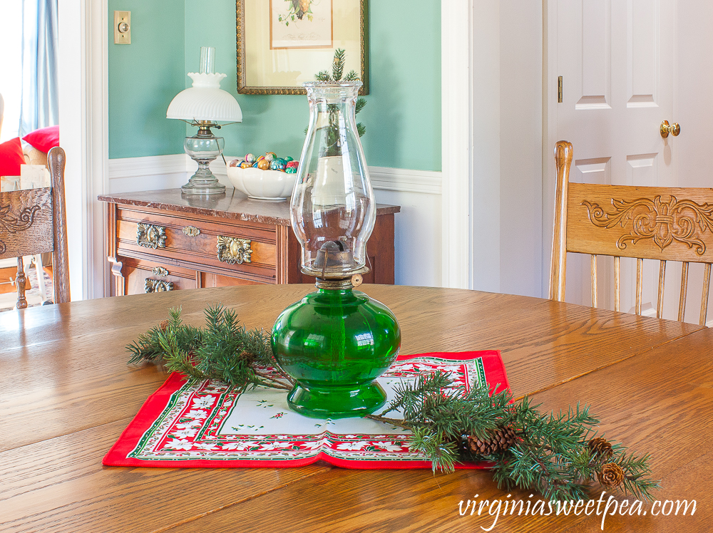 A Very Vintage Christmas in the Dining Room - Oil lamp with a green base used as a table centerpiece with a vintage Christmas napkin and greenery.