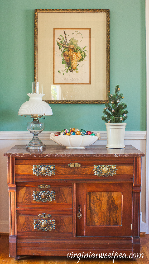 A Very Vintage Christmas in the Dining Room - Antique chest decorated for Christmas with vintage ornaments in a McCoy dish.