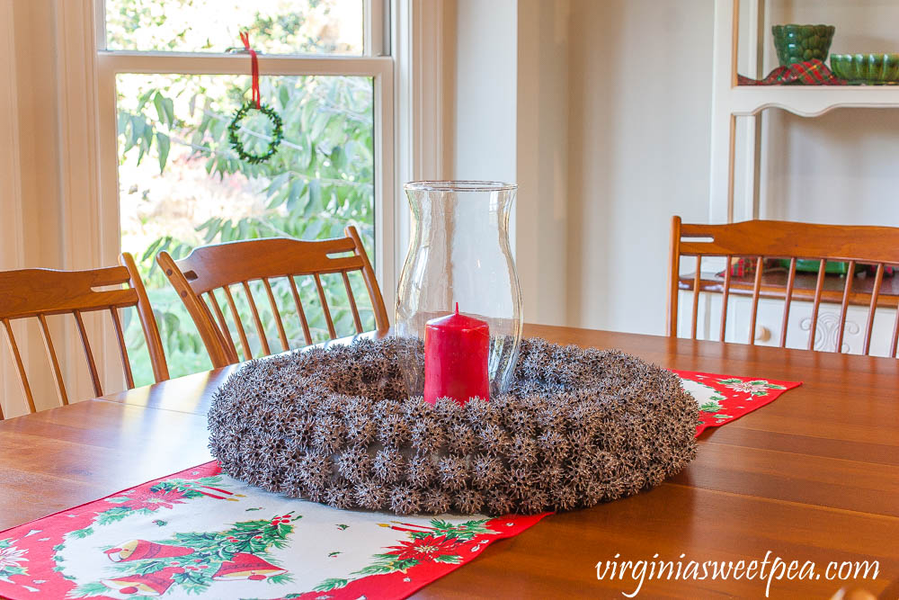 Wreath made from Sweet Gum balls with a glass hurricane and red candle on top of a vintage table runner.