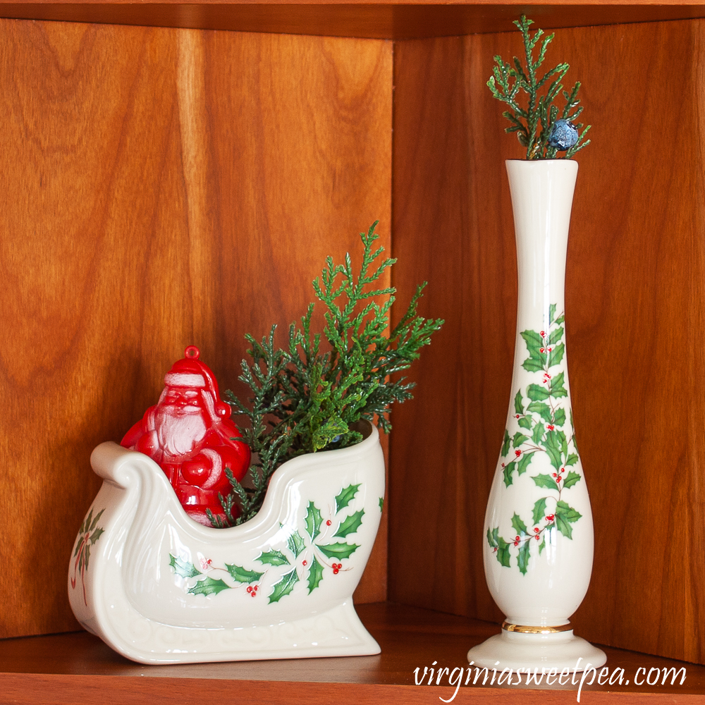 Kitchen shelf decorated for Christmas with Lenox Holiday pieces and a vintage Santa candy container.