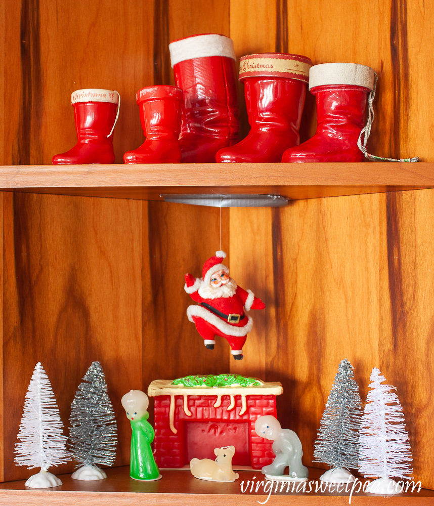 Kitchen shelves decorated for Christmas with vintage Santa boots, vintage style candles from The Vermont Country Store, a vintage Santa, and bottlebrush trees.