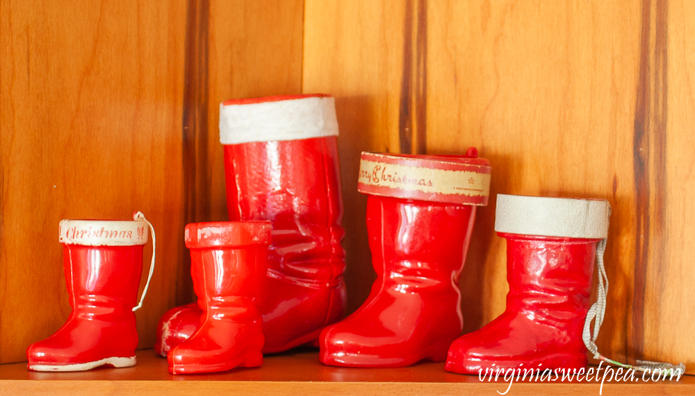 Collection of vintage Santa boots used to decorate a kitchen shelf.