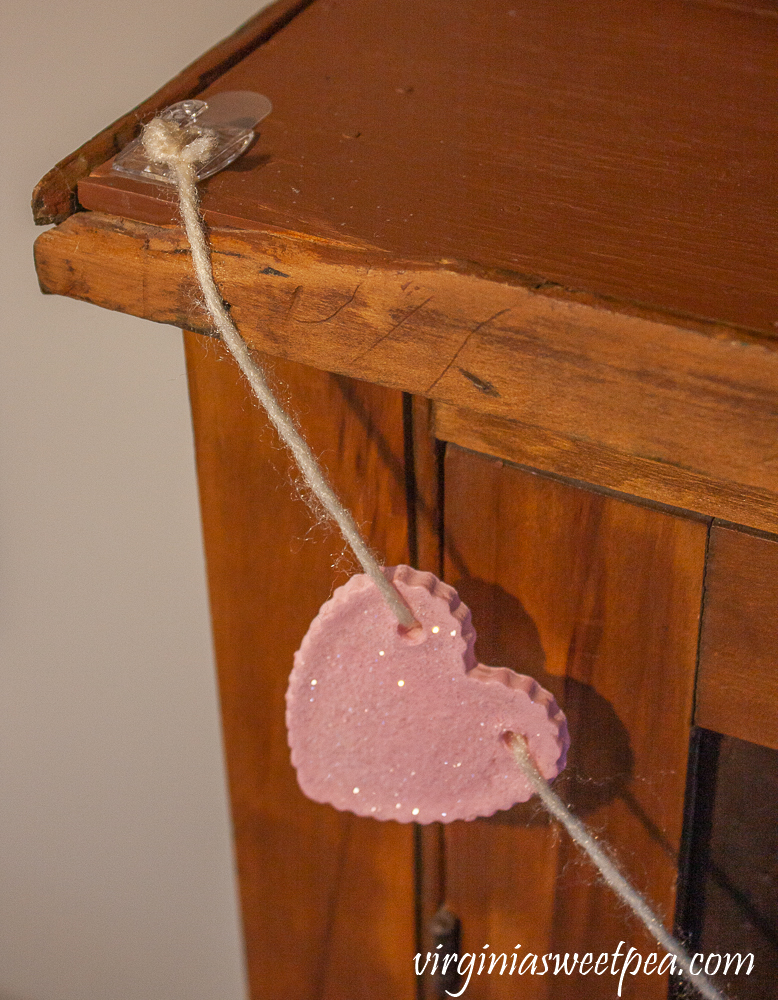 Hanging a heart garland with a command hook on an antique pie safe