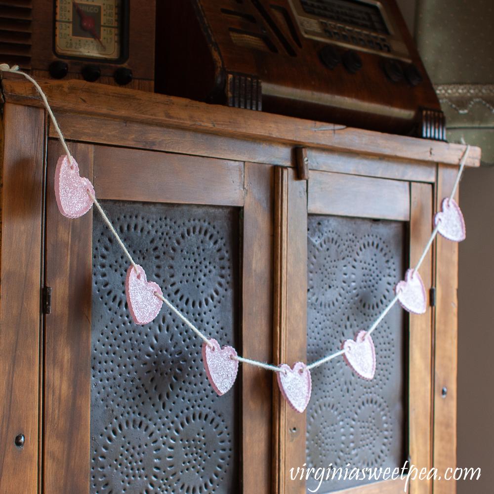 Heart Garland hanging on an antique pie safe