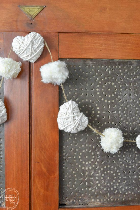 arn Heart and Pom Pom Garland hanging on a pie safe