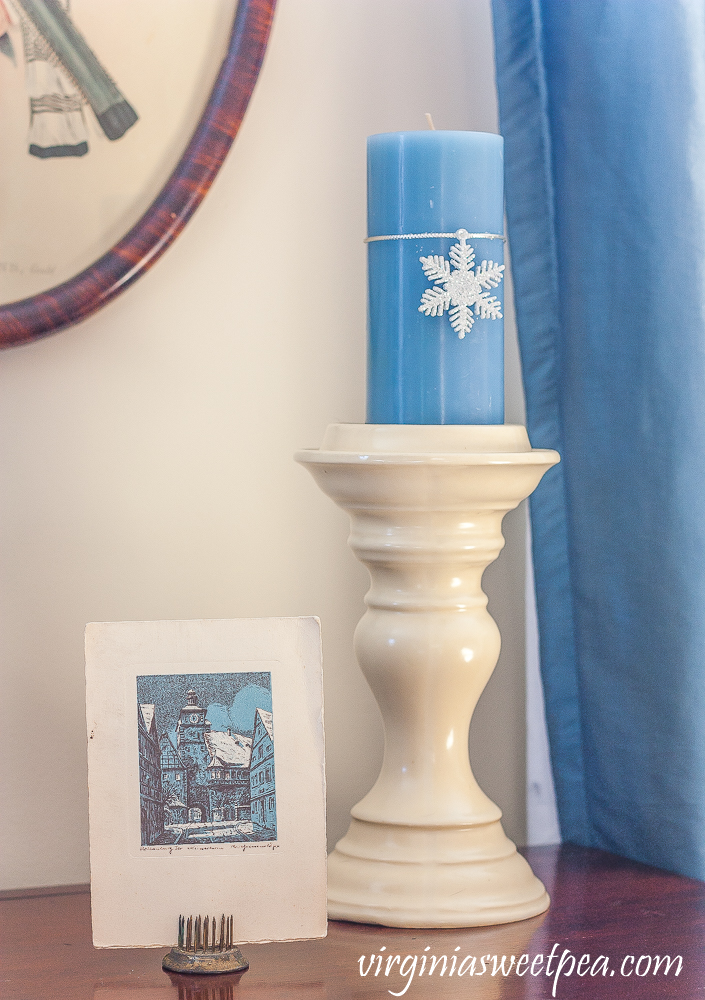 Vintage German Christmas card, cream candle holder with blue candle with a snowflake ornament tied to it.
