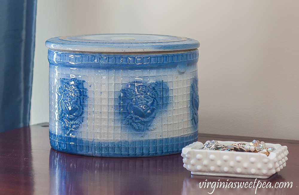 Blue and white antique crock with lid and a milk glass ashtray filled with vintage jewelry.