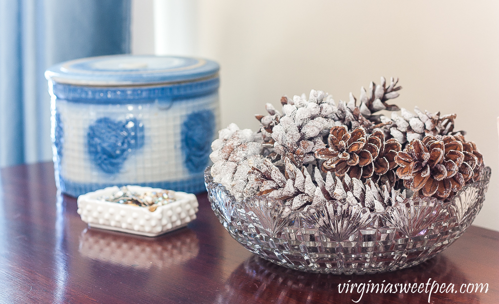 Blue and white antique crock with lid, milk glass ashtray filled with vintage jewelry, antique cut glass bowl filled with pine cones coated in faux snow.