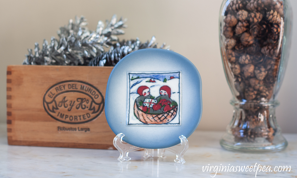 Finland plate with two children in a sled, cigar box filled with pine cones spray painted silver, a vintage glass candy jar filled with Hemlock pine cones