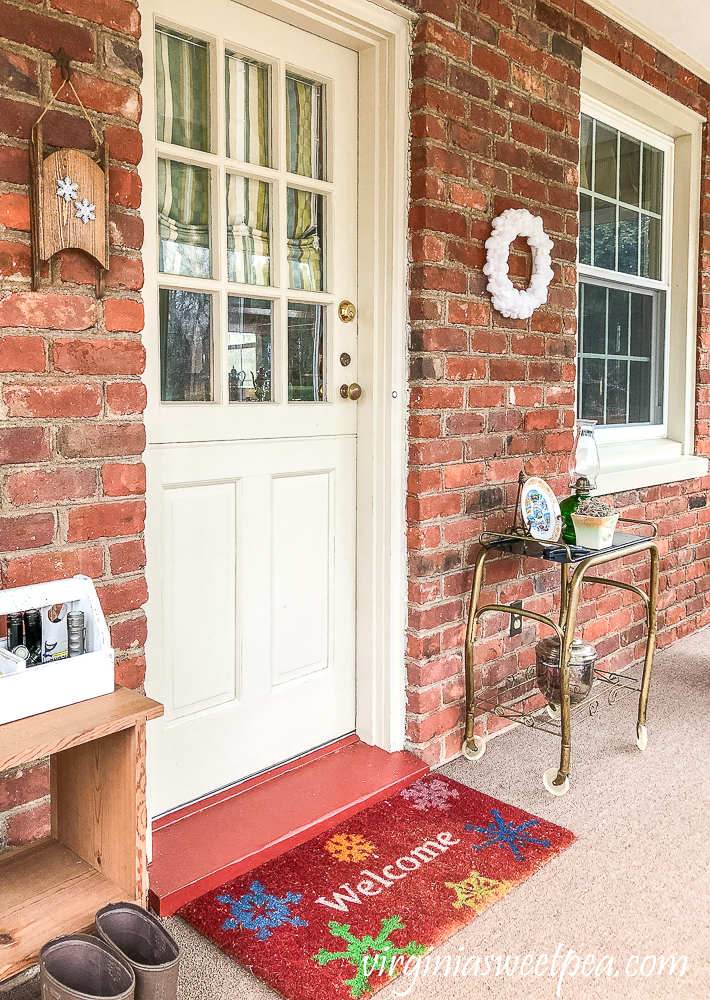 Easy DIY Pom Pom Wreath Displayed on an enclosed porch with brick walls