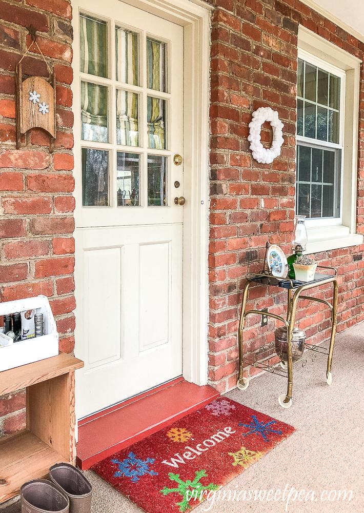 Easy DIY Pom Pom Wreath Displayed on an enclosed porch with brick walls