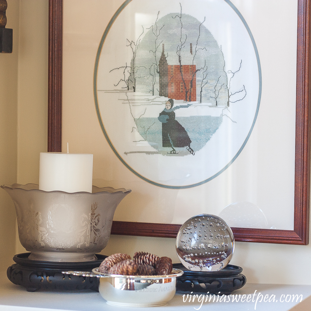 Silver child's porridge bowl, antique glass lamp shade, glass ball with bubbles in the glass, P. Buckley Moss cross stitch