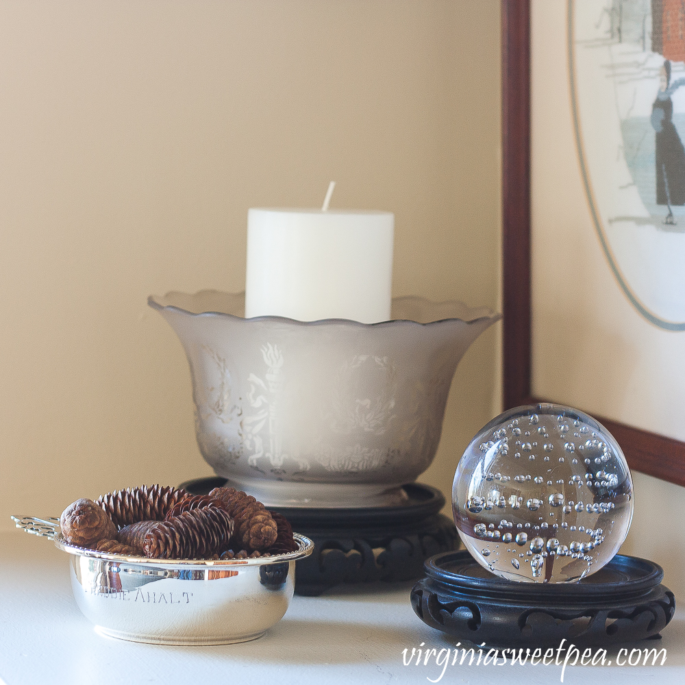 Silver child's porridge bowl, antique glass lamp shade, glass ball with bubbles in the glass.