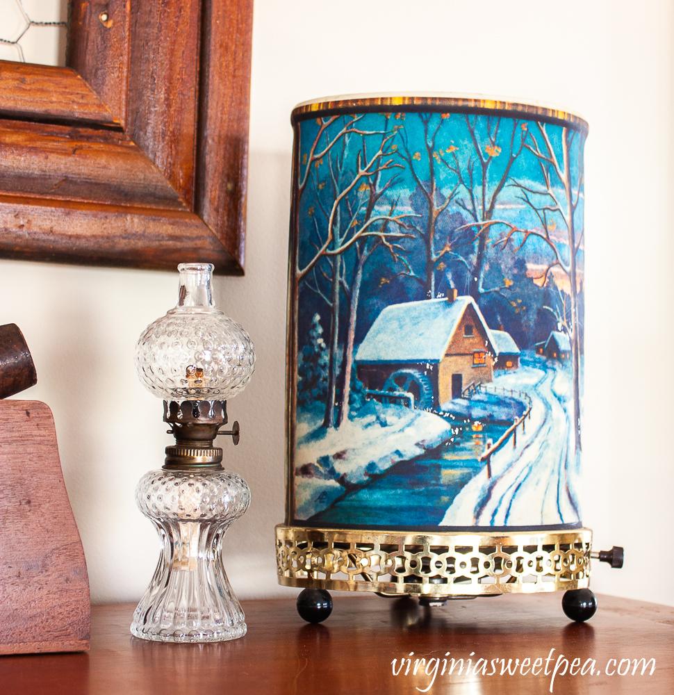 Vintage winter scene Econolite motion lamp and antique miniature oil lamp