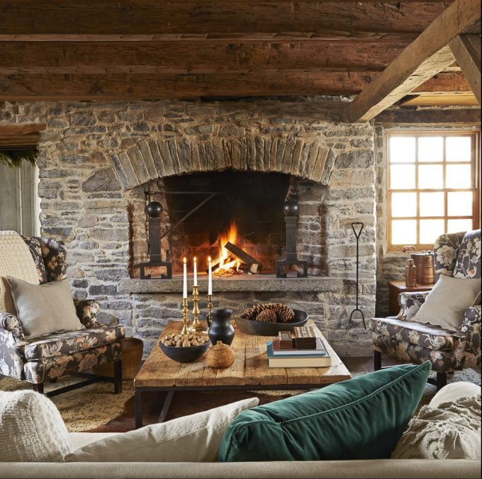 Rock fireplace in a cabin with a wood plank coffee table decorated for winter