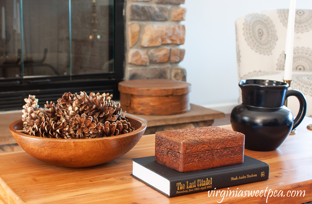 Winter coffee table decor with wood bowl filled with pine cones, carved wood box, black pitcher