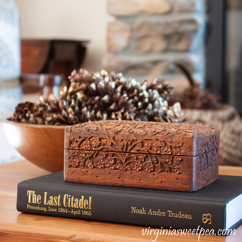 Winter coffee table decor with wood bowl filled with pine cones, carved wood box, and The Last Citadel book
