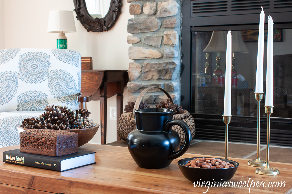 Winter coffee table decor with wood bowl filled with pine cones, carved wood box, black pitcher, black bowl with almonds, and three brass candlesticks with white candles