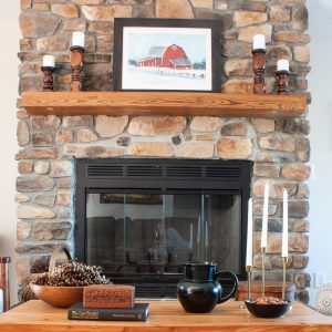 Rock fireplace with barn painting, wood candle holders, coffee table decorated for winter