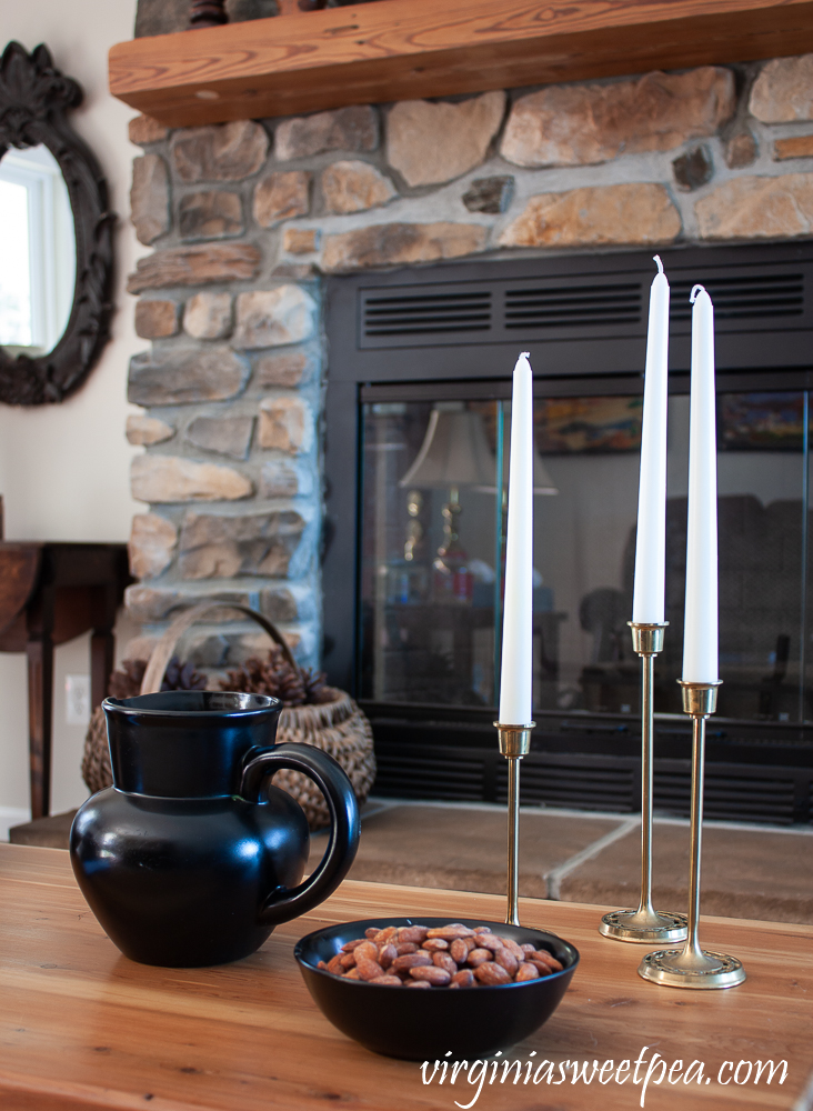 Vignette with black pitcher, black bowl filled with almonds, and three brass candlesticks with white candles