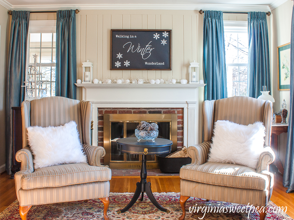 Winter mantel, wing back chairs with white fur pillows, a table with an antique glass compote filled with silver pinecones.