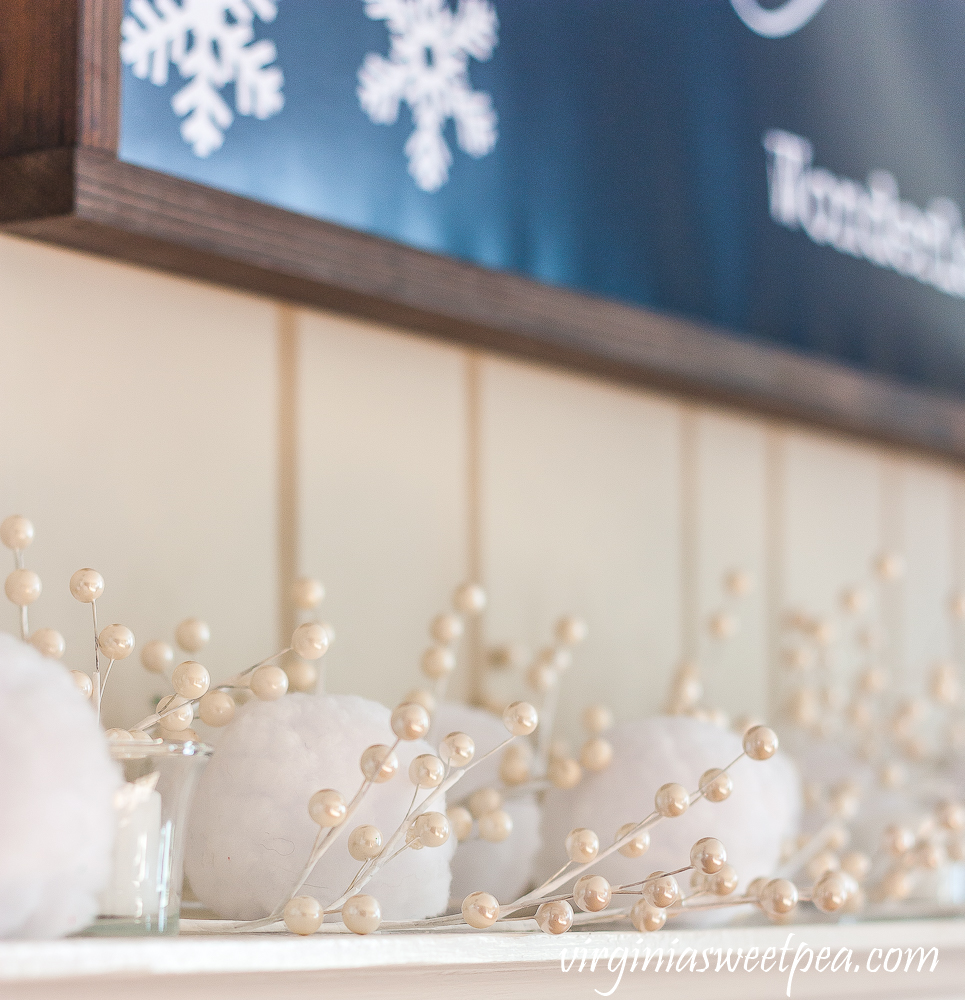 "Winter mantel with ""Walking in a Winter Wonderland"" sign, snowballs, and white berries."