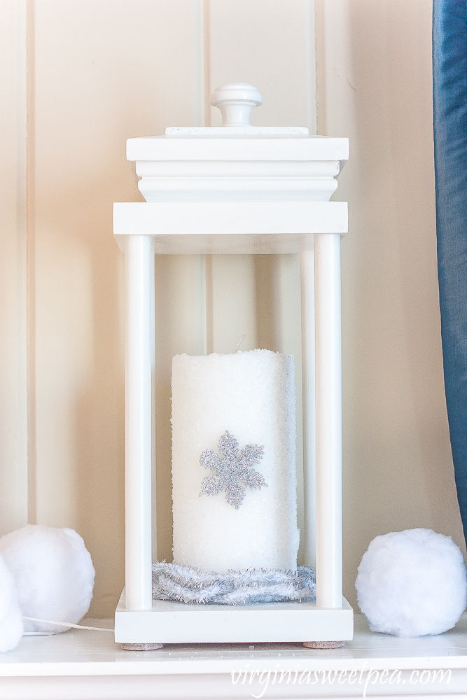 Lantern on a winter mantel with a candle covered in epsom salts with a snowflake surrounded by faux snowballs and faux berries.