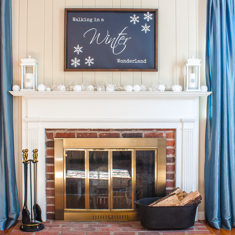 "Winter mantel with ""Walking in a Winter Wonderland"" sign, snowballs, lanterns, and white berries."