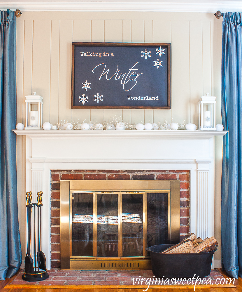 "Mantel styled for winter with a ""Walking in a Winter Wonderland"" sign, white lanterns and snowballs."