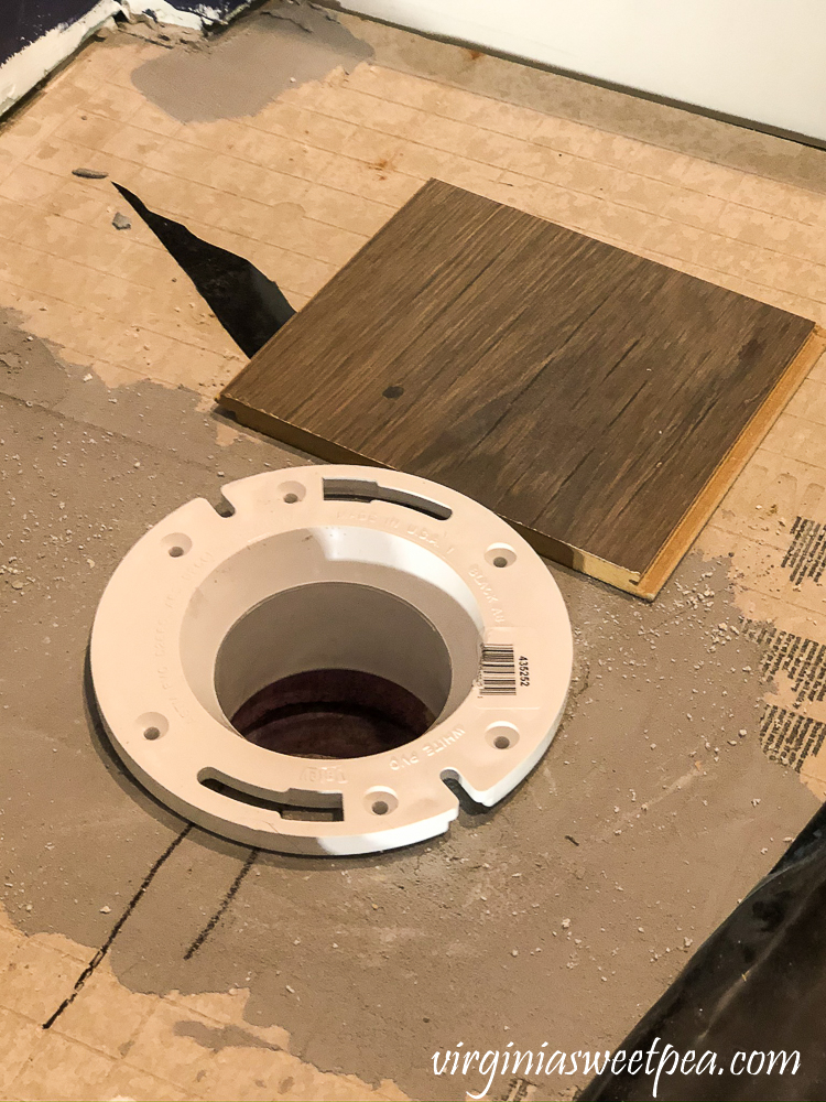 Preparing a toilet flange for flooring.