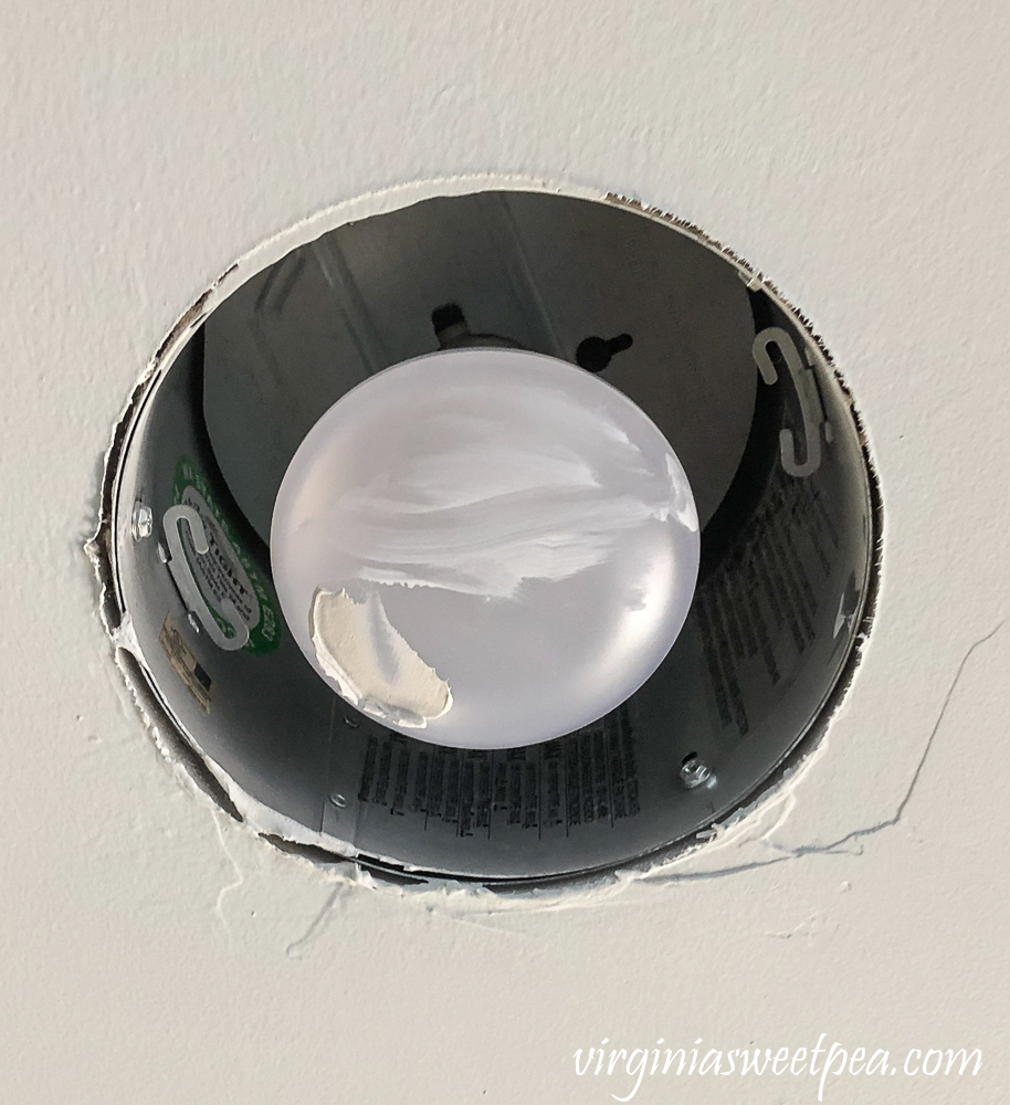 Can light bulb with ceiling paint and drywall mud on it.