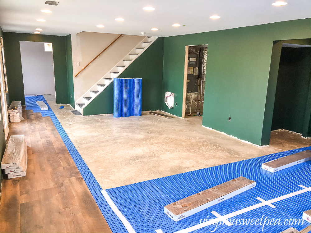 Basement with walls Painted with Sherwin Williams Emerald Paint in Rock Garden and floor installation with Mohawk Crest Loft in Prairie Oak