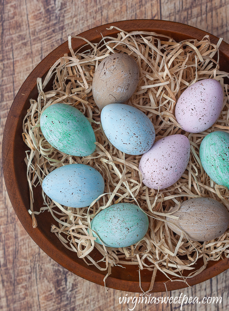 Speckled blue, green, and pink eggs in a wooden bowl filled with excelsior