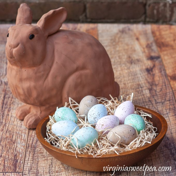 Speckled blue, green, and pink eggs in a wooden bowl filled with excelsior with a terracotta rabbit