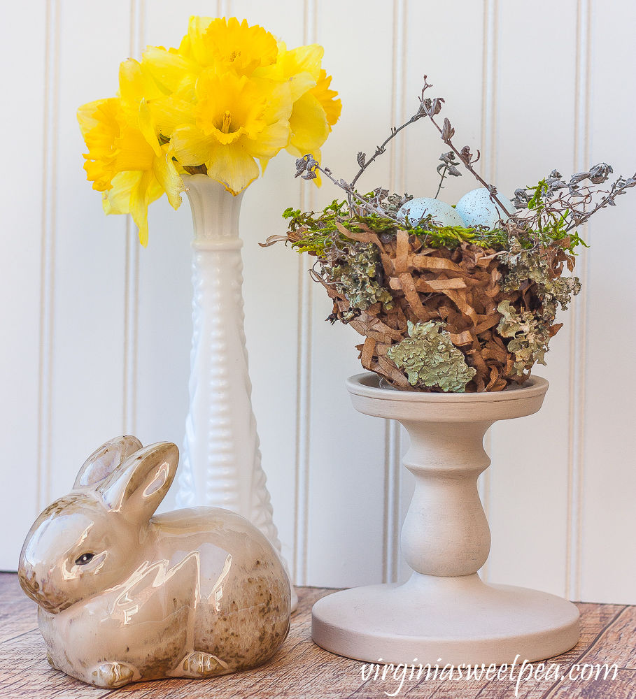 Spring vignette with rabbit, daffodils in a milk glass vase, and a nest.