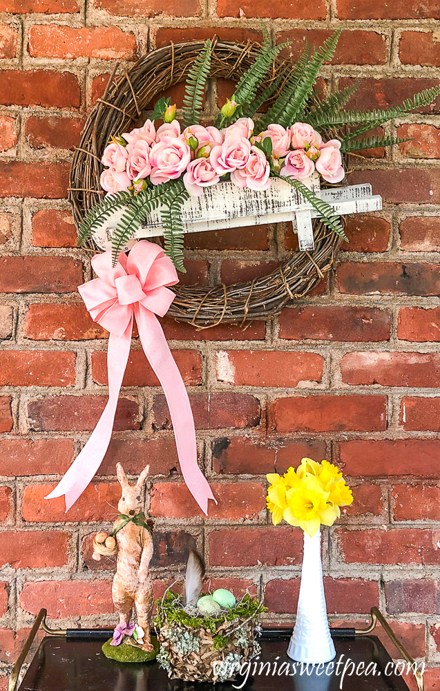 Spring wreath with a wheelbarrow filled with flowers.