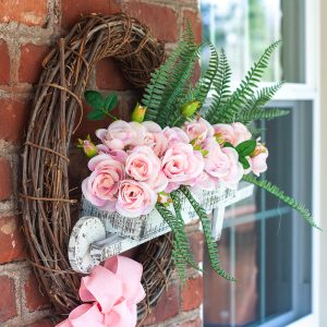Spring wreath with a wheelbarrow filled with flowers